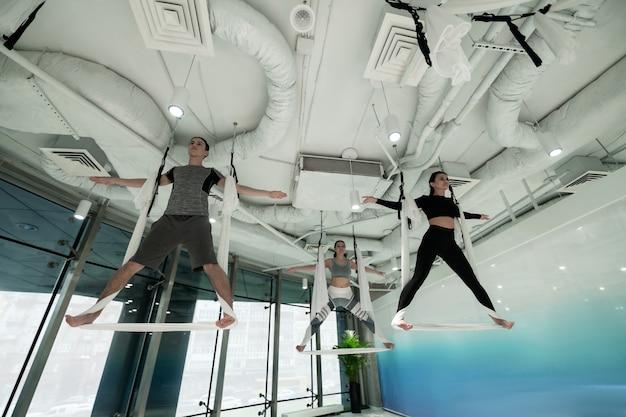 Ioga todo fim de semana. homem ativo e em forma e duas mulheres praticando ioga aérea todos os fins de semana