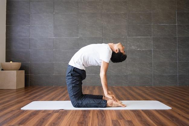 Iogue fazendo pose de ioga de camelo no ginásio