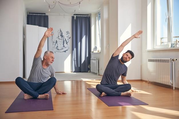 Iogue iniciante caucasiano focado na maturidade repetindo um exercício após seu instrutor pessoal em uma academia