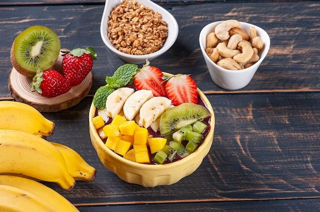 Iogurte brasileiro em uma tigela acompanhado de frutas tropicais. copie o espaço
