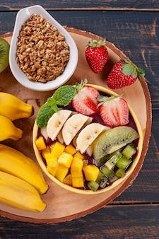 Iogurte brasileiro em uma tigela acompanhado de frutas tropicais. vista do topo