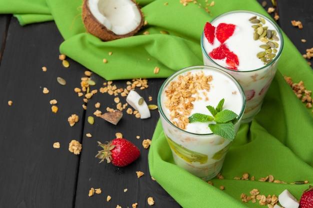 Iogurte caseiro com granola, frutas e coco vista superior na superfície de madeira