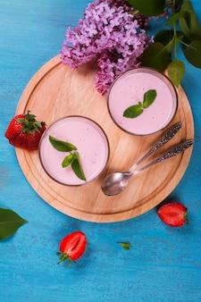 Iogurte caseiro com morango fresco e hortelã no fundo azul de madeira