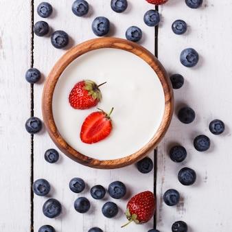 Iogurte caseiro, creme de leite em uma tigela de madeira de frutas