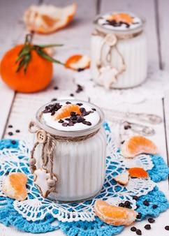 Iogurte caseiro em uma jarra com tangerinas e chocolate