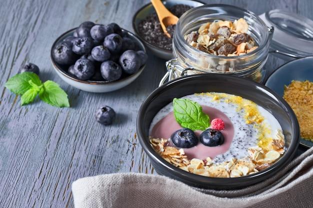 Iogurte com cereais, mirtilos, sementes de papoila, hortelã e flocos de milho esmagados, servidos em uma tigela preta brilhante