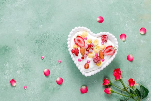 Iogurte com flocos de milho e frutas vermelhas em uma tigela em forma de coração.