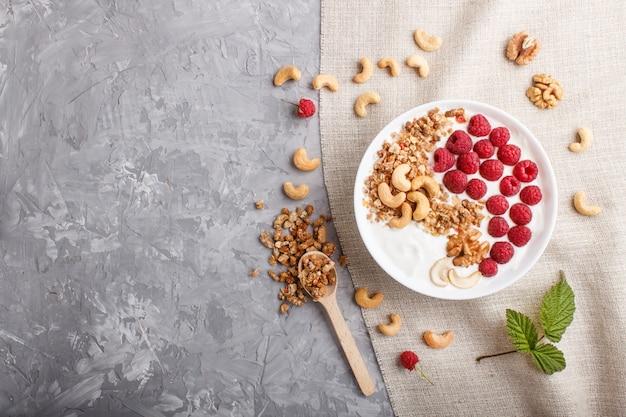 Iogurte com framboesa, granola, caju e nozes em chapa branca com colher de pau no fundo cinza concreto e têxteis de linho. vista do topo.