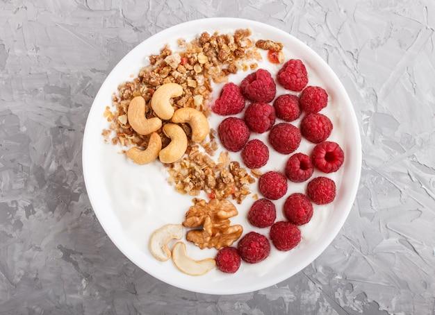 Iogurte com framboesa, granola, caju e nozes em chapa branca na superfície de concreto cinza e têxteis de linho. vista do topo.