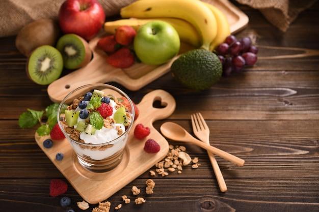 Iogurte com granola e frutas em vidro na mesa de madeira