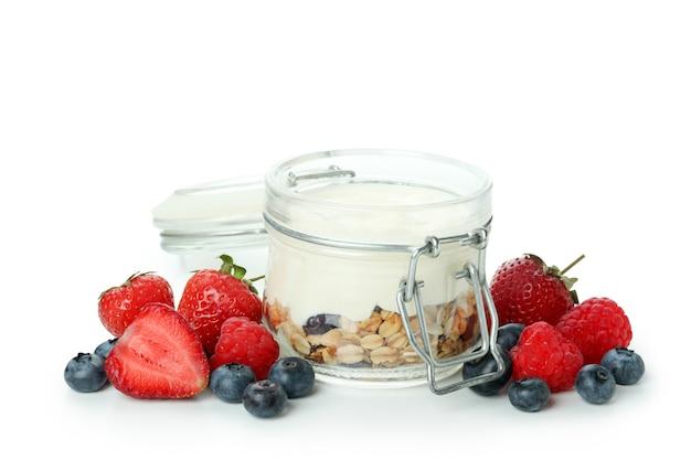 Iogurte com granola e frutas vermelhas isoladas no fundo branco