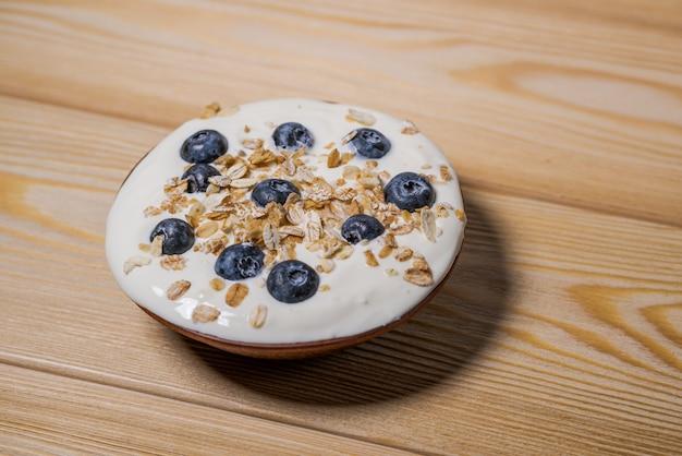 Iogurte com granola e mirtilos frescos, em tigela sobre fundo de madeira velho.