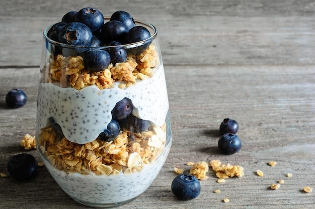 Iogurte com granola, mirtilos frescos, sementes de chia e aveia