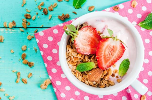 Iogurte com granola, nozes e morango fresco