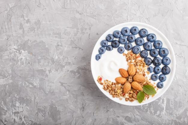 Iogurte com mirtilo, granola e amêndoa em chapa branca sobre fundo cinza de concreto. vista do topo.