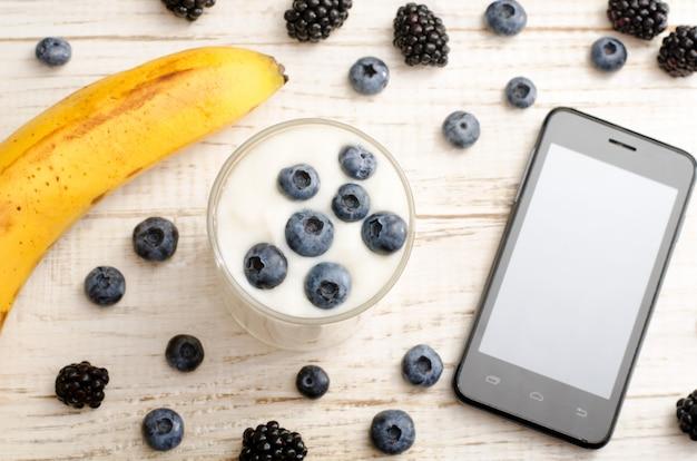 Iogurte com mirtilos, banana madura, smartphone e frutas em cima da mesa