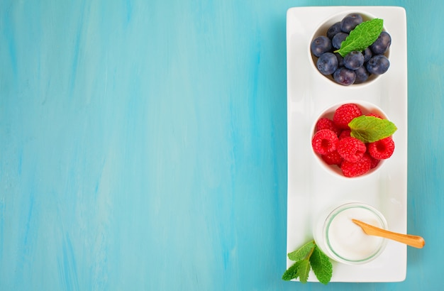 Iogurte com mirtilos e raspberies - conceito de saúde e dieta. café da manhã saudável equilibrado