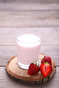 Iogurte com morango em vidro em cinza de madeira