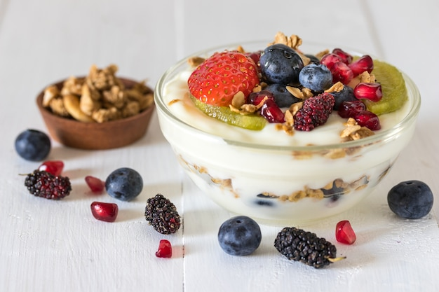 Iogurte com morango, mirtilos, kiwi, granola, romã em uma tigela de vidro e mel em madeira branca