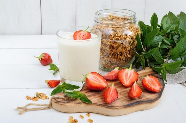 Iogurte com morangos e granola em cima da mesa