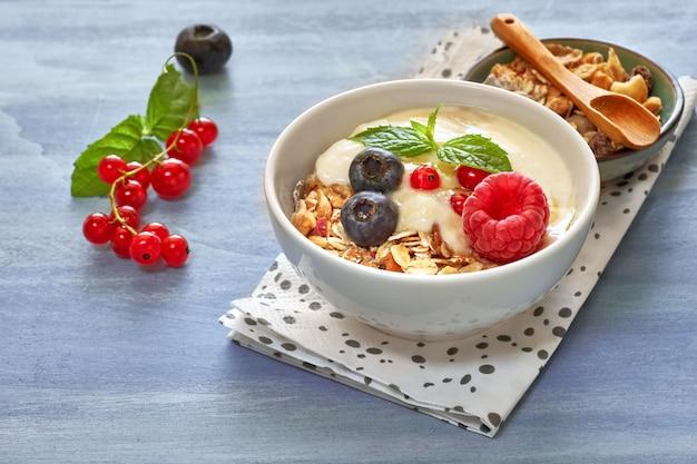 Iogurte com muesli e frutas, sobremesa saudável em madeira neutra