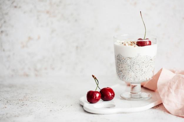 Iogurte com sementes de chia, aveia e cerejas sobre um fundo claro