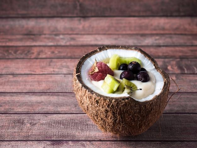 Iogurte de frutas nas metades de coco com frutas frescas em um fundo escuro de madeira