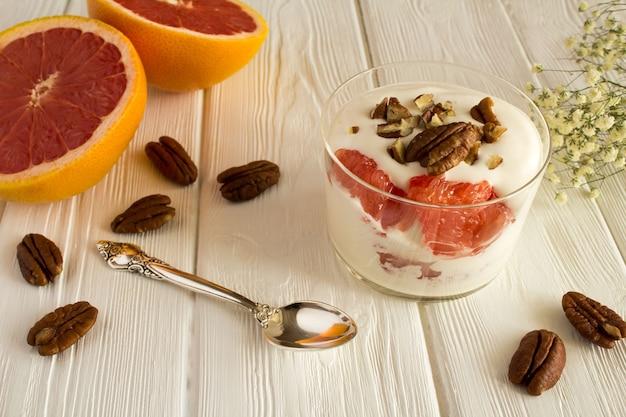Iogurte de leite com grapefruit e noz-pecã na madeira branca