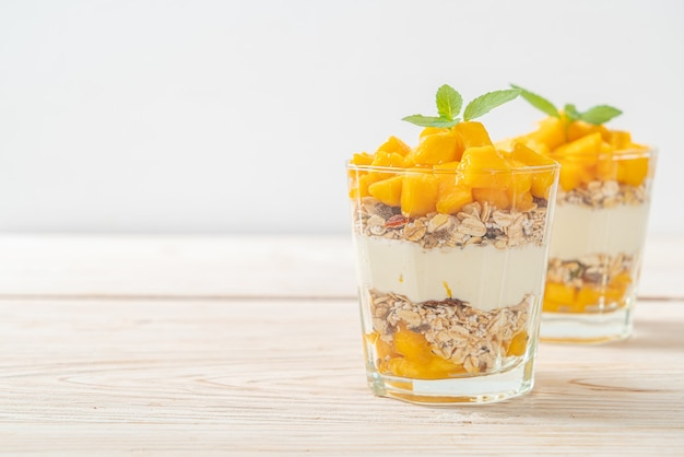 Iogurte de manga fresca com granola em vidro. estilo de comida saudável