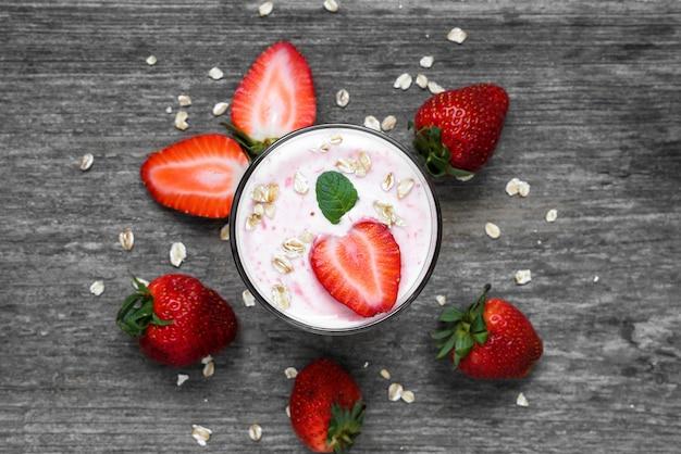 Iogurte de morango em um copo com frutas frescas, aveia e hortelã sobre fundo de madeira rústico
