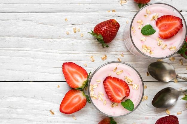 Iogurte de morango saudável com aveia e hortelã em copos com frutas frescas e colheres sobre a mesa de madeira branca