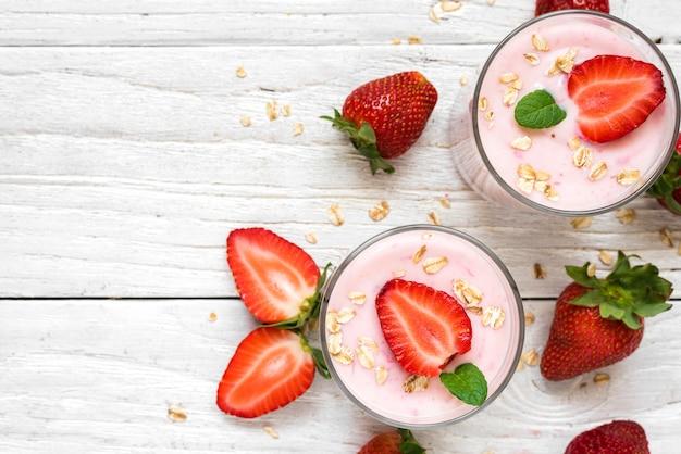 Iogurte de morango saudável com aveia e hortelã em copos com frutas frescas, mesa de madeira branca