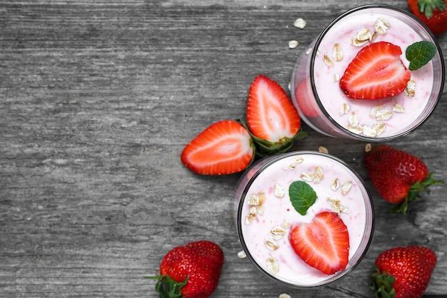 Iogurte de morango saudável com aveia e hortelã em copos com frutas frescas, mesa de madeira rústica