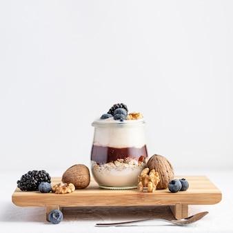 Iogurte de vista frontal com geléia e frutas a bordo