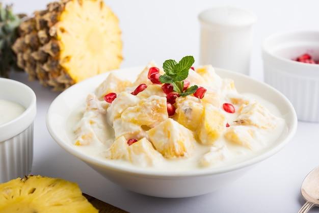 Iogurte e abacaxi ou ananas raita, servidos em tigela e enfeitados com hortelã e romã, sobre fundo colorido ou de madeira. foco seletivo