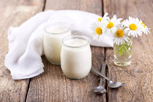 Iogurte em potes de vidro na mesa de madeira