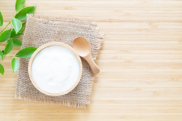 Iogurte em tigela de madeira na mesa de madeira branca