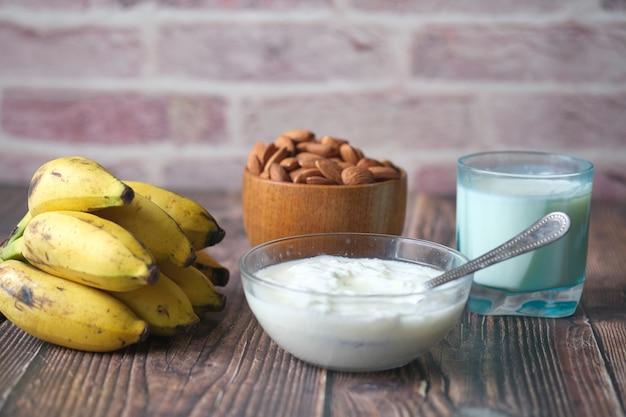 Iogurte fresco em uma tigela com banana de amêndoa e leite na mesa ab