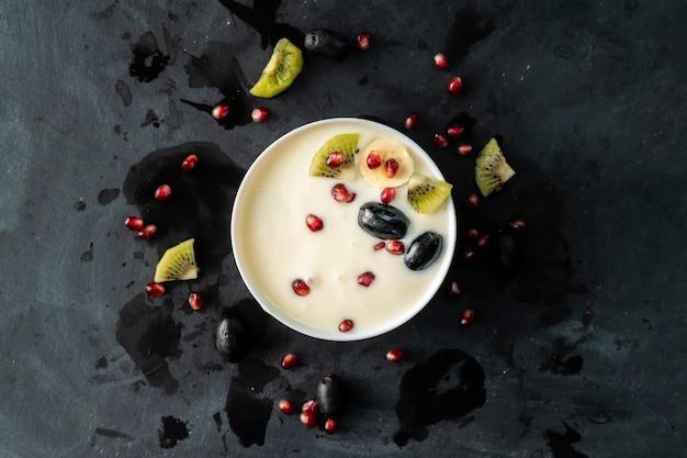 Iogurte fresco leve em uma tigela de cerâmica com pequenos pedaços de frutas tropicais, kiwi, banana, granada, grapess