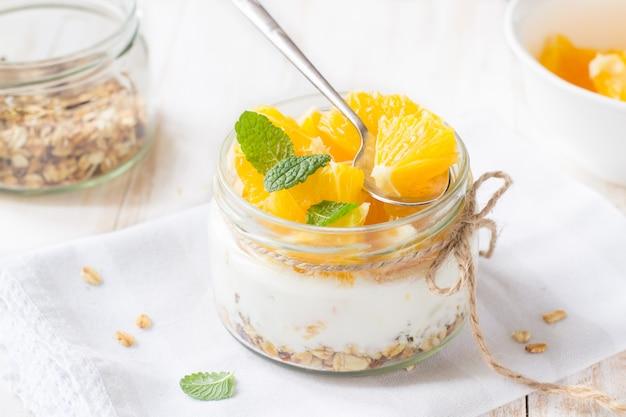 Iogurte, granola e laranja em frasco de vidro
