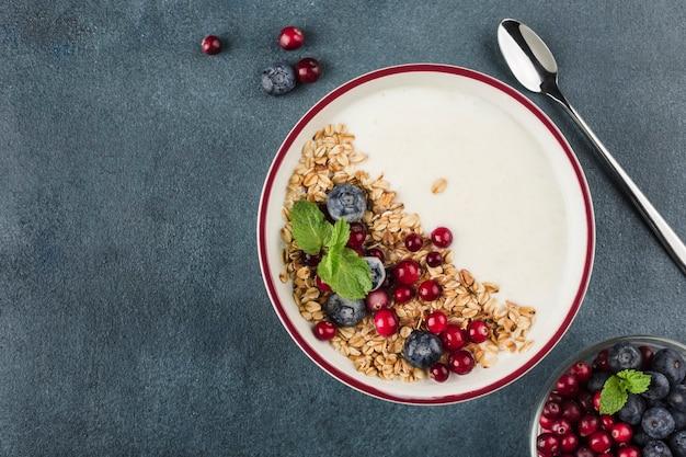 Iogurte grego com granola, mirtilos frescos, cranberries e hortelã em um prato com uma colher em um fundo azul escuro. um café da manhã leve para dieta e preparo físico. vista superior com um espaço de cópia para o texto.