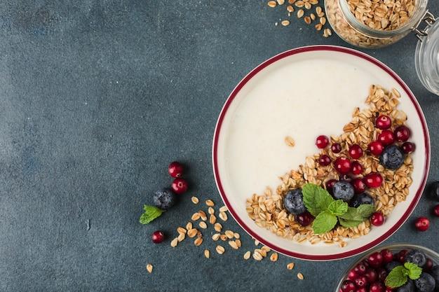 Iogurte grego com granola, mirtilos frescos, cranberries e hortelã em um prato sobre um fundo azul escuro. um café da manhã leve para dieta e preparo físico. vista superior com um espaço de cópia para o texto.