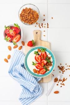 Iogurte grego em uma tigela branca com ingredientes para fazer granola de café da manhã e morangos frescos na mesa branca. vista do topo