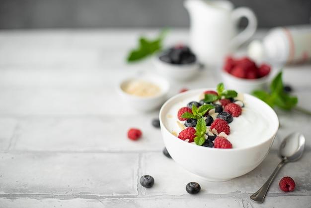 Iogurte grego fresco com mirtilos, framboesas e hortelã