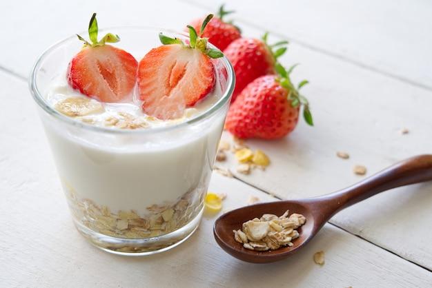 Iogurte grego saudável com morango e muesli no vidro em uma tabela de madeira velha da vista lateral.