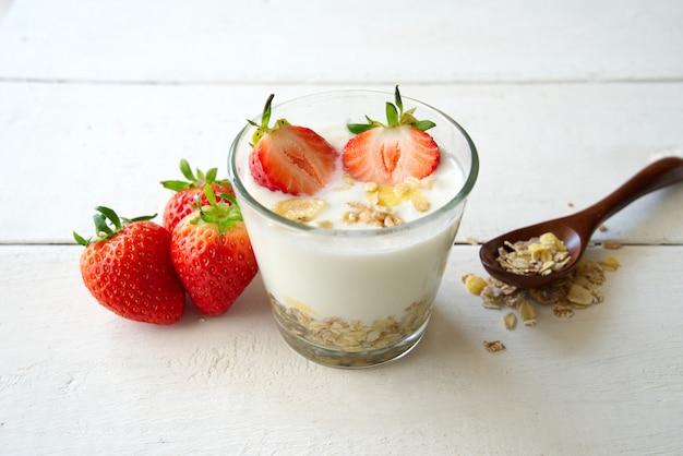 Iogurte grego saudável com morango e muesli no vidro em uma tabela de madeira velha na vista dianteira.