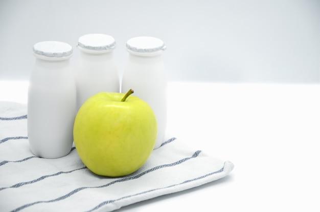 Iogurte líquido natural com probióticos em pequenas garrafas de plástico e maçã amarela