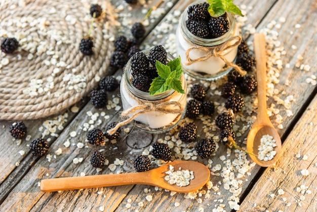 Iogurte matinal com adição de amoras maduras. em uma mesa de madeira.