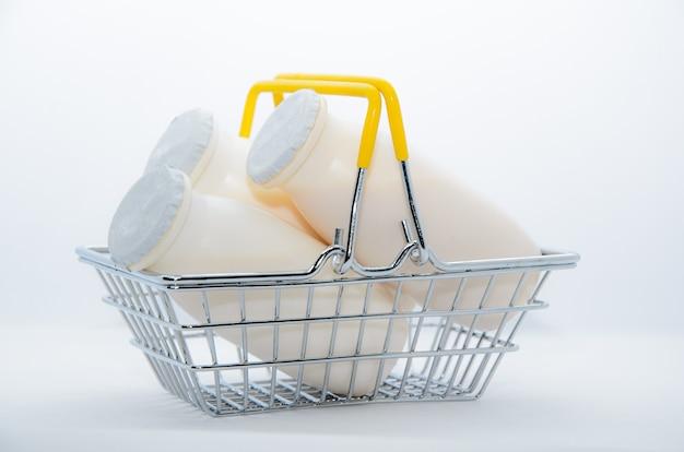 Iogurte natural com probióticos e lactobacillus em pequenas garrafas plásticas em uma cesta de metal na cor branca