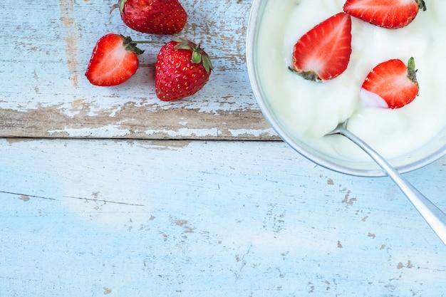 Iogurte natural e frutas de morango no fundo de madeira